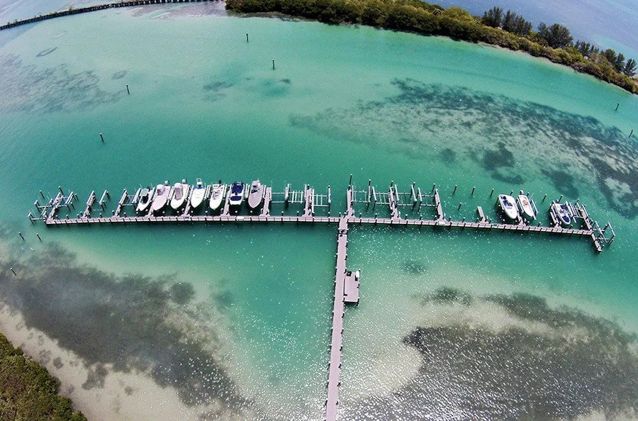 dock on blue water with boats in florida